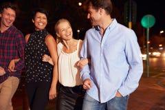 Quatre amis marchant par la ville ensemble la nuit Images stock