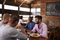 Quatre amis masculins au déjeuner ensemble dans le restaurant, se ferment  Photographie stock
