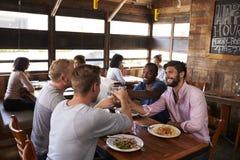 Quatre amis masculins faisant un pain grillé à une table dans un restaurant Images libres de droits