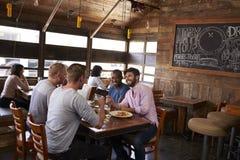 Quatre amis masculins s'asseyant au déjeuner ensemble dans un restaurant Photographie stock