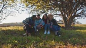 Quatre amis multiraciaux s'asseyant à la zone rurale Images libres de droits