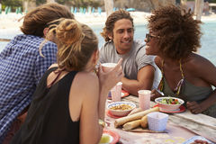 Quatre amis parlant à une table par la mer, vue de côté, Ibiza Photo libre de droits