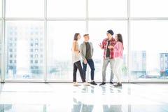 Quatre amis parlant dans le hall lumineux avec les fenêtres panoramiques Image stock