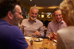 Quatre amis parlant ensemble pendant un repas à un restaurant Photos libres de droits