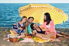 Quatre amis partagent la nourriture et les boissons sur la plage Photo libre de droits