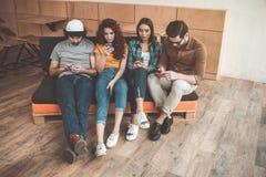 Quatre amis préfèrent l'Internet plutôt que la vraie conversation Image stock