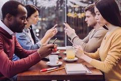 Quatre amis réfléchis textotant dans le media social Photo libre de droits