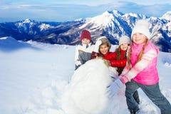 Quatre amis roulant la boule de neige énorme sur la colline Image stock