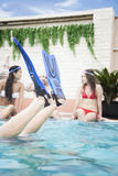 Quatre amis s'asseyant dans la piscine, pieds avec des nageoires dans le ciel Images stock