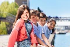 Quatre amis s'asseyant dans une ligne sur la banque de la rivière Photographie stock