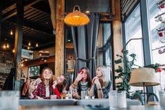 Quatre amis s'asseyant par la table en café et faisant le selfie sur le smartphone Photos libres de droits