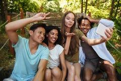 Quatre amis s'asseyant sur des escaliers dans la forêt Images libres de droits
