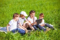 Quatre amis s'asseyant sur l'herbe Images stock