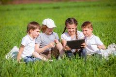 Quatre amis s'asseyant sur l'herbe Photo stock