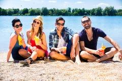 Quatre amis s'asseyant sur la plage de lac avec des cocktails Image stock