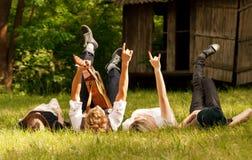 Quatre amis se situant dans l'herbe Photographie stock libre de droits
