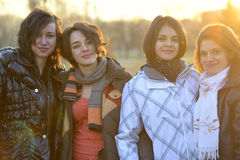 Quatre amis se tenant ensemble pendant le coucher du soleil Photos libres de droits