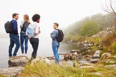 Quatre amis sur une hausse marchant par le bord d'un lac Photo libre de droits
