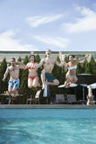 Quatre amis tenant des mains et sautant dans une piscine, entre le ciel et la terre Photos stock
