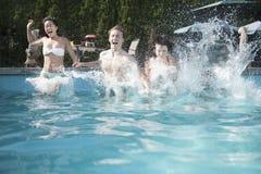 Quatre amis tenant des mains et sautant dans une piscine, entre le ciel et la terre Image stock
