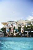 Quatre amis tenant des mains et sautant dans une piscine, entre le ciel et la terre Photos libres de droits