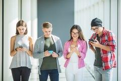 Quatre amis travaillant à la société étant dépendante des instruments, utilisant les téléphones et le comprimé intelligents pour  Images stock