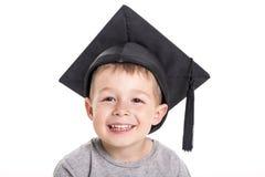 Quatre années adorables de garçon d'enfant portant un panneau de mortier Photos stock