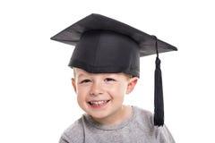 Quatre années adorables de garçon d'enfant portant un panneau de mortier Images stock