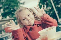 Quatre années de fille ayant l'amusement tout en mangeant Photographie stock