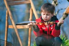 Quatre années de garçon mange les légumes grillés Image libre de droits