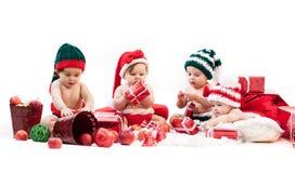 Quatre bébés dans des costumes de Noël jouant parmi des cadeaux Photo libre de droits