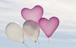 Quatre ballons remplis par hélium contre le ciel Photographie stock
