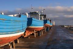 Quatre bateaux de pêche bleus dans la réparation de attente de dock sec Photos stock