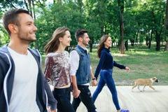 Quatre beaux amis marchant en parc tenant des mains Image libre de droits