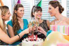 Quatre beaux et femmes gaies grillant avec le champagne Photo libre de droits