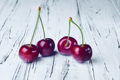 Quatre belles cerises rouges sur une table en bois blanche Photo stock