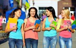 Quatre belles filles d'université marchant sur la rue Photo libre de droits