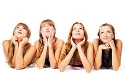 Quatre belles filles s'étendant sur l'étage ensemble Photo libre de droits