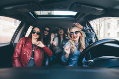 Quatre belles jeunes femmes gaies regardant l'un l'autre avec le sourire tout en se reposant dans la voiture images stock
