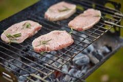 Quatre biftecks crus sur le gril Images stock
