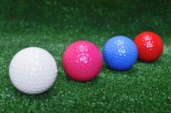 Quatre billes de golf dans la ligne image stock