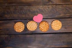 Quatre biscuits ronds et coeur rose faits de papier Photographie stock libre de droits