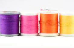 Quatre bobines de fil coloré Images stock