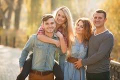 Quatre bons amis détendent et ont l'amusement en parc d'automne Image libre de droits