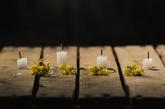 Quatre bougies blanches de cire se reposant sur la surface en bois, aucune flammes brûlant, avec le fond noir, le bel arrangement Photographie stock