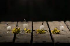 Quatre bougies blanches de cire se reposant sur la surface en bois, aucune flammes brûlant, avec le fond noir, le bel arrangement Image stock