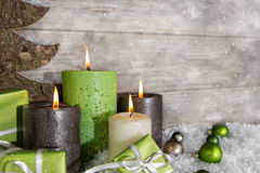 Quatre bougies brûlantes d'avènement dans vert et brun sur le backgro en bois Photographie stock