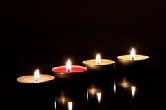 Quatre bougies brûlantes dans l'obscurité Photos stock
