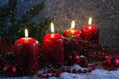 Quatre bougies rouges d'avènement brûlant sur un conseil en bois rustique avec s Photo libre de droits