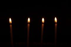 Quatre bougies sur l'obscurité Image libre de droits